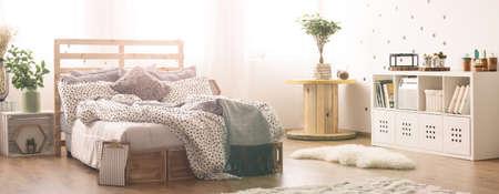 Heldere moderne slaapkamer met rommelig palletbed Stockfoto