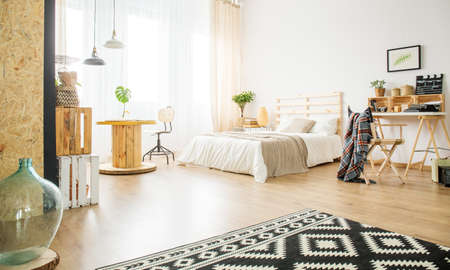 Spacious studio apartment interior with wooden and upcycled accessories