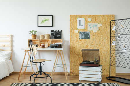 Modern light room with wooden desk and osb board with posters