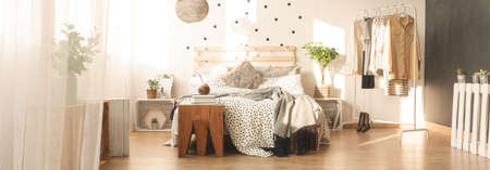 messy clothes: Handmade pallet bed and dotted bedroom wall