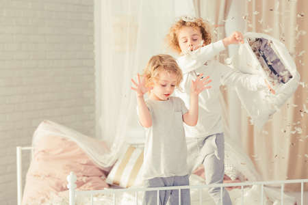 Brothers having pillow fight and making mess in bedroom