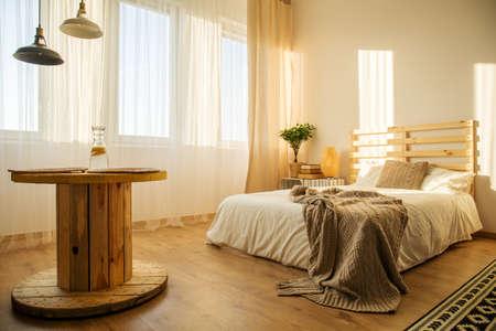 ダブルベッドと白とベージュの寝室の木製のテーブル