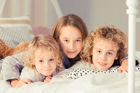 untidy: Sister hugging her two little brothers on the bed