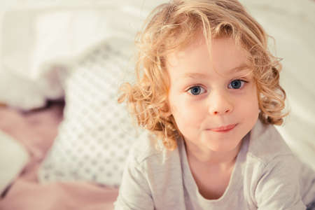 untidy: Little boy with blonde curly hair sitting on the bed