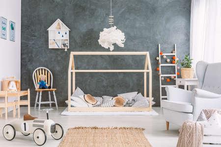 Gezellige kinderkamer met veel speelgoed en grijze muur