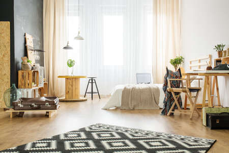 Creative interior of upcycled studio apartment with bed and wooden furniture Stock Photo