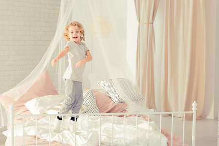 untidy: Little boy smiling and jumping on the bed