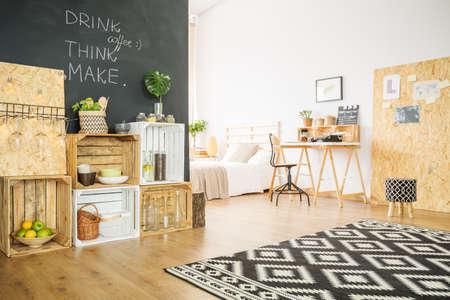 Creatieve open ruimte van een studio-appartement met houten meubilair
