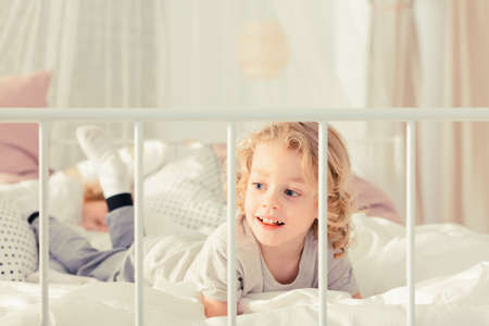untidy: Little boy laying on the bed and smiling
