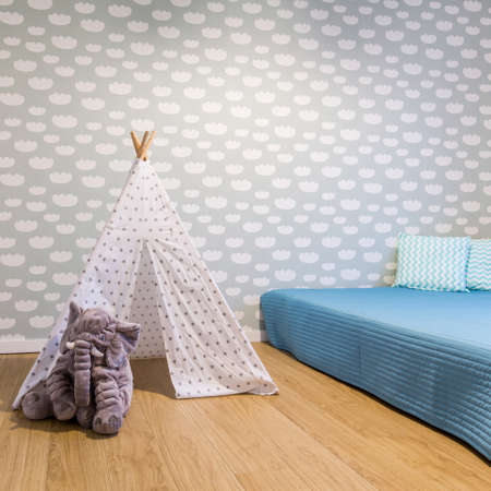 Beautiful and cozy room for a child with tipi tent, blue bed and cloud wallpaper