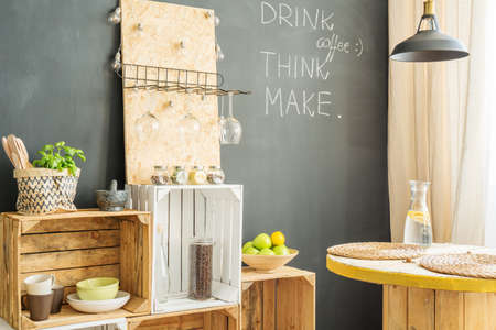 Wooden crates and table in modern kitchen with blackboard wall Stock Photo