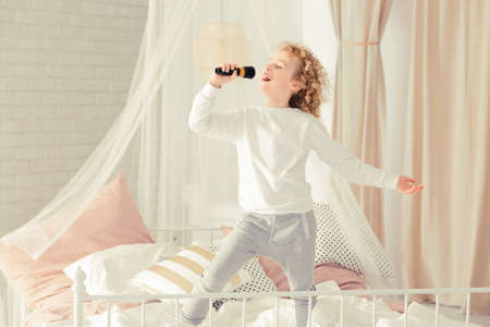 untidy: Little boy standing on the bed and singing
