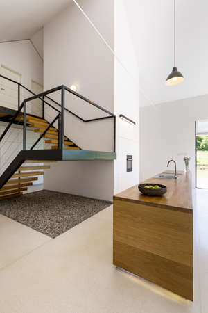 entresol: Spacious house interior with a modern minimalist kitchen and a staircase Stock Photo