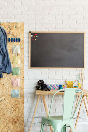 Interior with brick wall, blackboard, desk, chair and OSB board Stock Photo