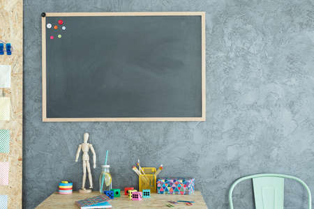 Gray home office with blackboard, wood desk and chair Stock Photo