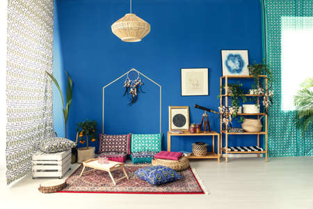 Postcolonial home interior with colorful pattern pillows and wood bookcase 版權商用圖片