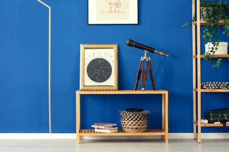 Blaues zimmer mit musterteppich altes teleskop bücherregal aus