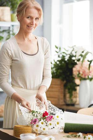 Happy, professional florist working in her own flower studio