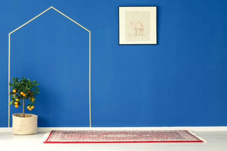 ascetic: Ascetic interior with blue wall, poster, pattern rug, citrus tree