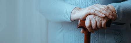 Close-up van senior gehandicapte vrouw handen met een stokje