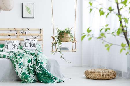 Witte slaapkamer met rotan poef, schommel en een tweepersoonsbed Stockfoto