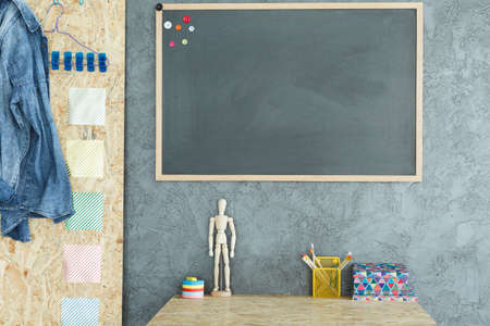 Gray interior with OSB board, desk and blackboard