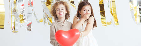 Happy young boy and girl in love with heart balloon