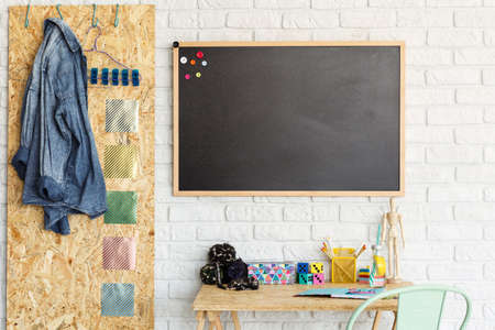 Interior with brick wall, desk, chair, blackboard, OSB board