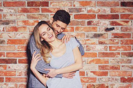 赤レンガの壁の背景に一緒に幸せな若いカップル 写真素材