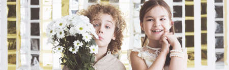 Little boy holding the flowers for his happy girlfriend Stock Photo
