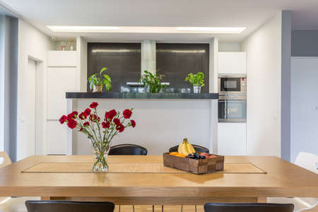 Open plan kitchen with the kitchen island and wooden table at the foreground Stock Photo - & Open Plan Kitchen With The Kitchen Island And Wooden Table At ...