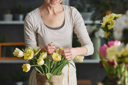 Woman decorating bouquet of yellow tulips in sack Stock Photo