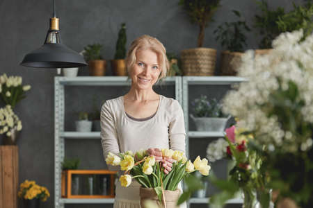 yourself: Smiling florist and bouquet if yellow tulips in sack