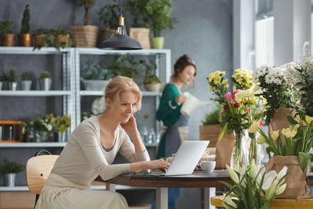 Mooie bloemist die in bloemwinkel werkt, die laptop met behulp van