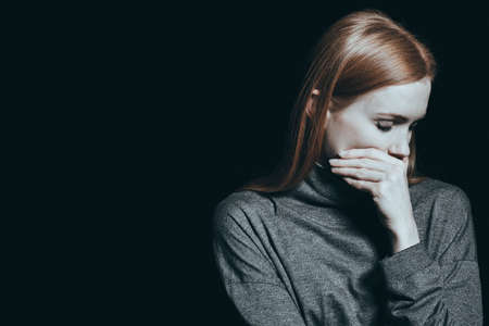 Bulimic woman covering her mouth, black background