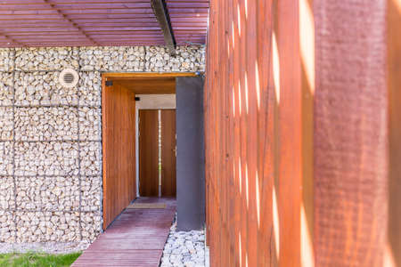 Entrance to a modern stone house with wooden pergola