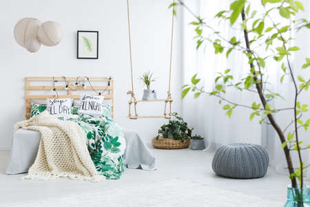 Bedroom with gray pouf, plants, double bed, lamp and swing Imagens