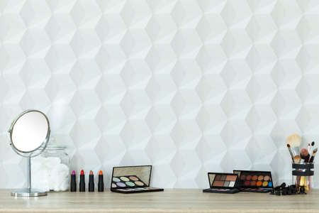 Colorful cosmetics and mirror lying on table, white background Banco de Imagens