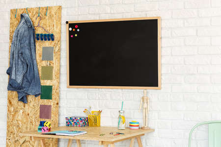 Modern workspace with brick wall, osb board, blackboard and chair