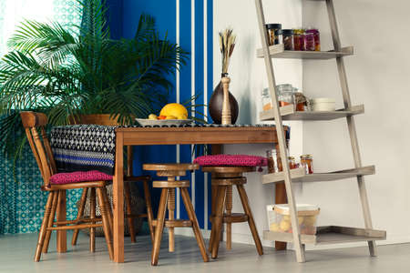 Kamer met ladder boekenkast, houten tafel, stoelen en plant