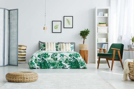 White bedroom with screen, bed, armchair, bookcase, lamp and pouf Stockfoto