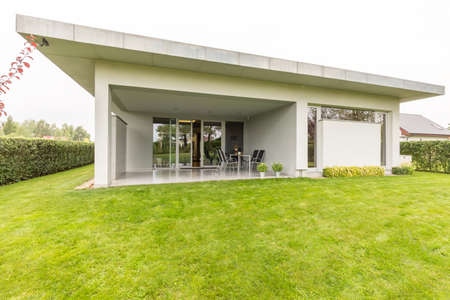 Modern house with the covered terrace, surrounded by grass