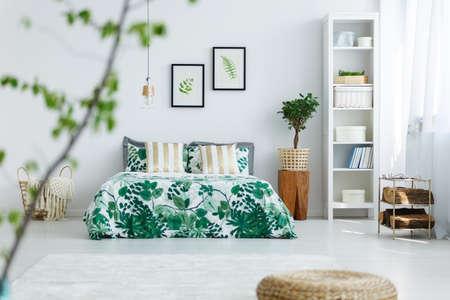 책장, 식물, 더블 침대 및 트렌디 한 침구가있는 흰색 침실