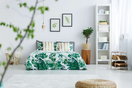 White bedroom with bookcase, plant, double bed and trendy bedding 版權商用圖片