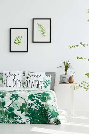 Witte slaapkamer met bladposters, groene planten en trendy beddengoed