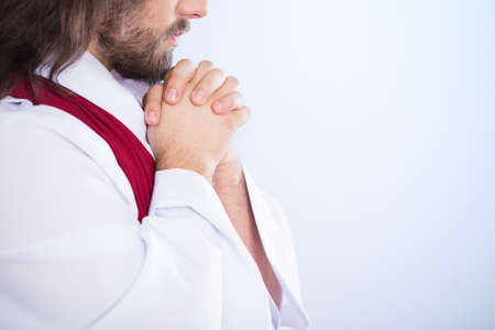 Lord on a bright background praying alone with folded hands