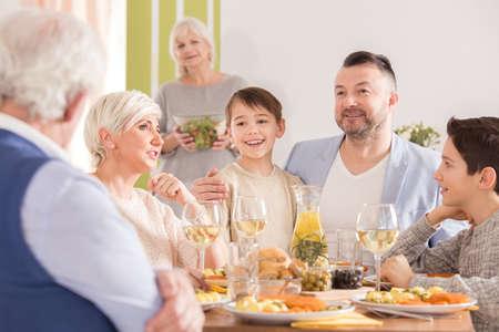 Grandma looking at the family talking at the table