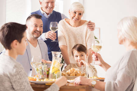 Grandpa making a toast at a happy family dinner