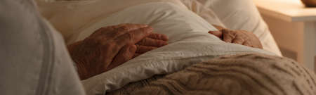 Senior people holding hands on a bed