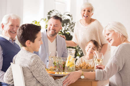 Happy family praising and congratulating boy at the dinner